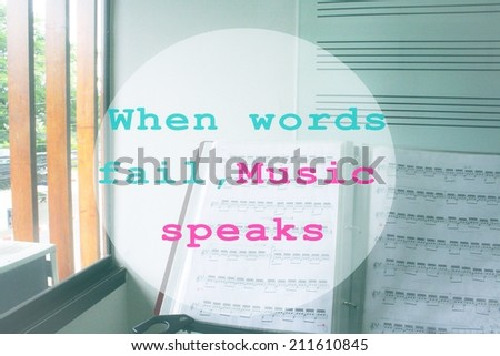 Inspirational motivating quote with sheet music and music staff blackboard as background:When words fail,Music speaks - stock photo