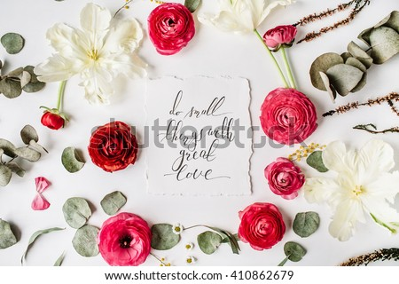 "inspirational quote ""Do small things with great love"" written in calligraphy style on paper with pink, red roses, ranunculus, white flowers and leaves isolated on white background. Flat lay, top view - stock photo"