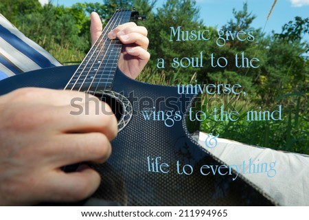 Inspirational quote on music by Plato, with a man's hand playing a guitar outside in his hammock in the summer.