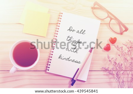 Inspirational quote on notebook and coffee cup on wooden table with vintage filter - stock photo