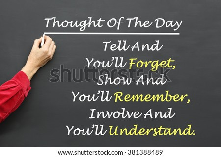 Inspirational Thought For The Day message of Tell And You'll Forget, Show And You'll Remember, Involve And You'll Understand written on a School Blackboard by the teacher. - stock photo