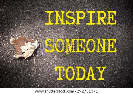 INSPIRE SOMEONE TODAY motivational quote. Yellow paint line on the road against asphalt background. Concept image