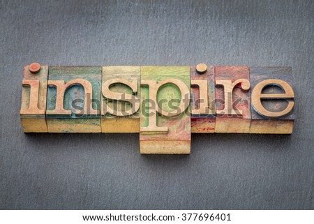 inspire word  in letterpress wood type printing blocks stained by color inks against slate rock background - stock photo