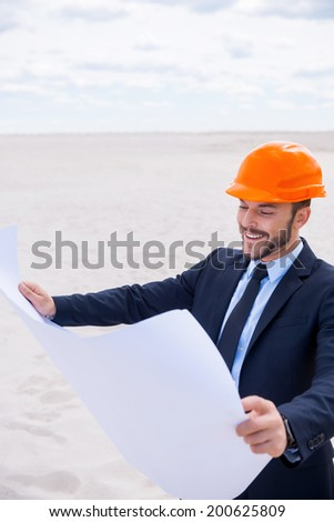 Inspired architect. Cheerful young man in formalwear and hardhat examining blueprint while standing in desert - stock photo