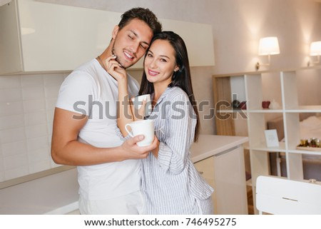 Inspired brunette girl stroking husband's face while he drinks coffee. Indoor portrait of married couple in pajamas having fun in kitchen during breakfast.