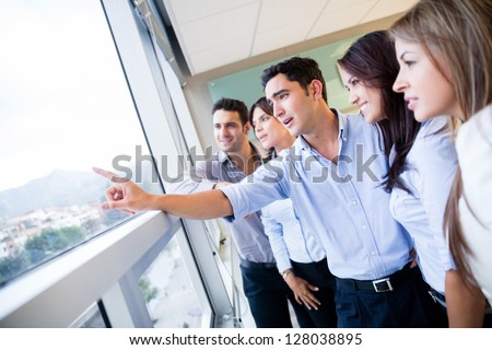 Inspired business group at the office looking through the window - stock photo
