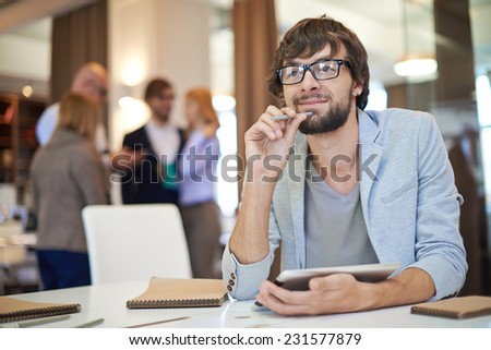 Inspired businessman in casual sitting at workplace in office - stock photo