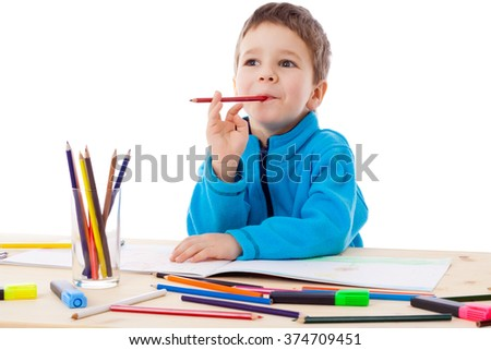 Inspired little boy at the table draw with crayons, isolated on white