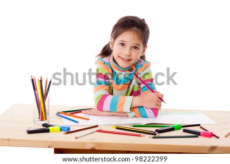 Inspired little girl at the table draw with crayons, isolated on white - stock photo