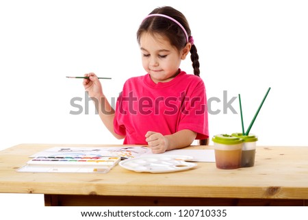 Inspired little girl who draws with watercolors at the table, isolated on white - stock photo