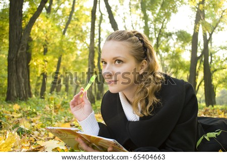 Inspired teenager girl lies in autumn park - stock photo