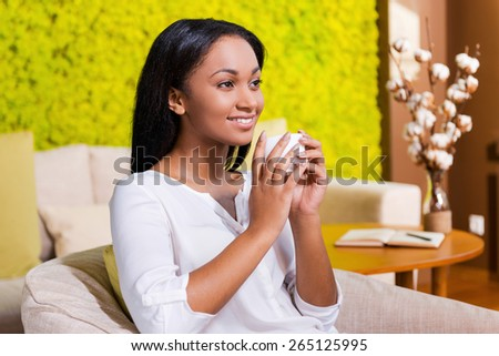 Inspired with cup of fresh coffee. Cheerful young African woman drinking coffee and looking away while sitting at the chair at home - stock photo