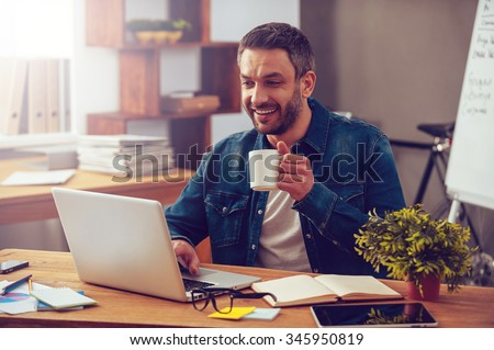 Inspired with cup of fresh coffee. Confident young man working on laptop and holding coffee cup while sitting at his working place in office - stock photo