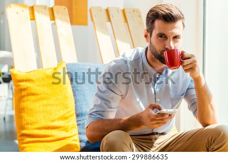 Inspired with cup of fresh coffee. Handsome young man holding mobile phone and drinking coffee while sitting in the rest area of the office - stock photo