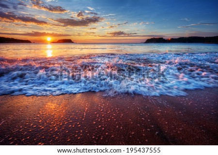 Inspiring and dynamic ocean bay sunrise on a secluded beach with fabulous sand and breaking wave - stock photo