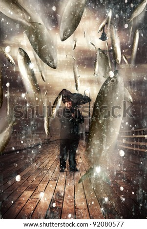 Inspiring And Imaginative Portrait Of A Senior Man Holding A Broken Umbrella On A Bridge Or Pier While Fish Pour Down From Stormy Skies In A Depiction Of A Miracle - stock photo