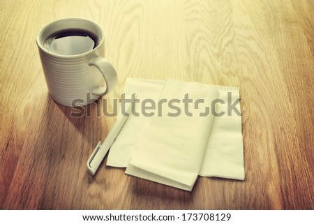 Instagram effect - white napkin or serviette and pen on oak surface, ideal for notes and phone numbers, and that great idea you had at the coffee shop. With mug of coffee. Focus on centre. - stock photo
