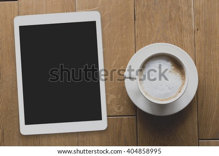 Instagram filter, digital tablet and coffee cup on wooden table, above view