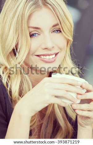 Instagram filter style beautiful smiling young woman with blond hair and blue eyes drinking coffee or tea from a white cup