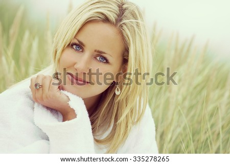 Instagram filter style photograph of a beautiful blond haired blue eyed girl or young woman wearing a white toweling robe sitting in tall grass  - stock photo