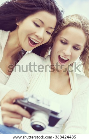 Instagram filter style photograph of two young women girls, one Asian Chinese, one blond, laughing looking at photographs on digital camera - stock photo