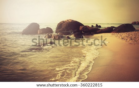 instagram filtered image from the coastline by the seaside with big boulders in the sand and the sunrise in the distance - stock photo