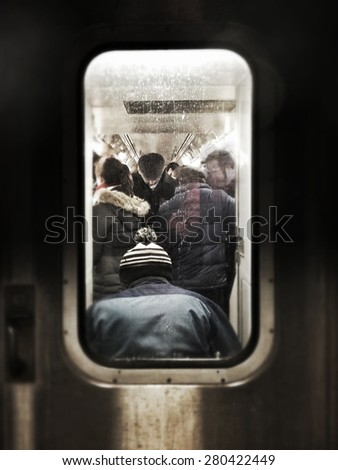 Instagram filtered image of a crowded subway car with commuters - stock photo
