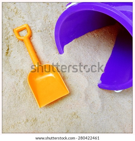 Instagram filtered image of a to shovel and pail in the sand - stock photo
