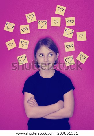 Instagram girl with sticky notes hearts around her head representing her thoughts of love - stock photo