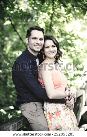 Instagram look of an image showing a happy young couple embracing on a bridge in a wooded setting - stock photo