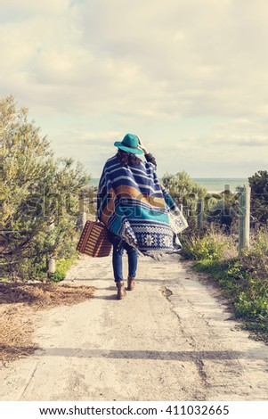 Instagram looking picture of young hipster girl in poncho with vintage suitcase walking toward see. Instagram looking effect, filters, selective focus, lifted shadows, color toning - stock photo