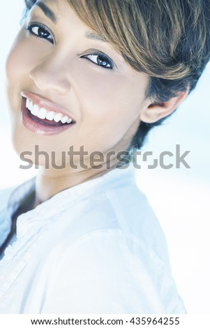 Instagram style photograph of beautiful mixed race young woman with perfect teeth laughing shot on a tropical beach - stock photo