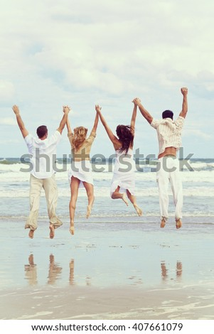 Instagram style photograph of four young people, two couples, holding hands, having fun and jumping in happy celebration on a beach
