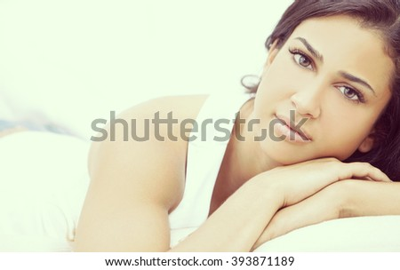 Instagram style portrait of a beautiful young Latina Hispanic young woman or girl looking thoughtful resting on her hands - stock photo