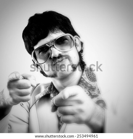 Instagram style portrait of a retro man in a 1970s leisure suit and sunglasses pointing to the camera - black and white - stock photo