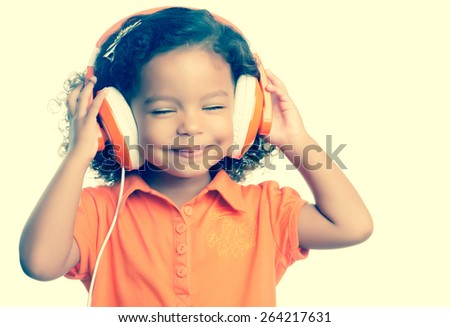 Instagram toned small girl listening to music on her big headphones - stock photo