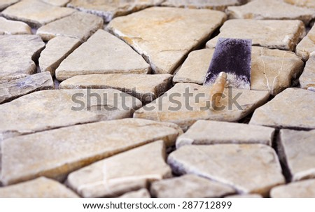 Instalation of decorative natural stone surface on a floor - stock photo