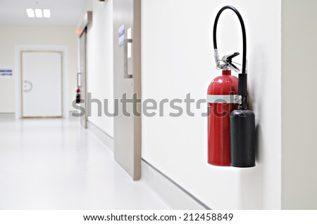 Install a fire extinguisher on the wall in building - stock photo