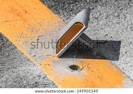 Install road stud with yellow reflector - stock photo