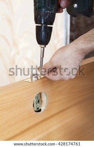 Installation door knob with lock, woodworker screwed screw, using  screwdriver. - stock photo