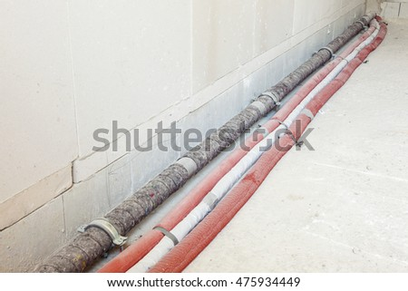 Installation of cables and pipes on the floor of a new house
