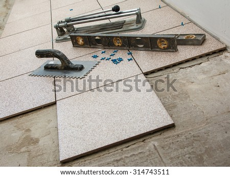 Installation of floor tiles. Ceramic tiles and different tools - stock photo