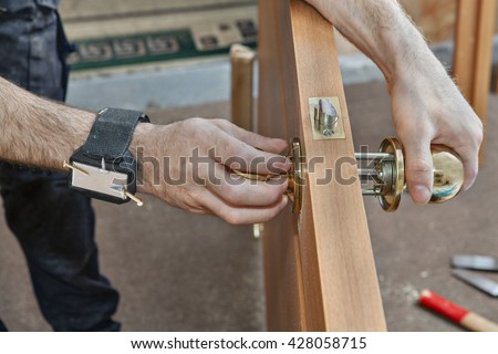 Installation of interior door, a carpenter installs handle with a lock in the door leaf using magnetic bracelet for holding screws, close-up. - stock photo