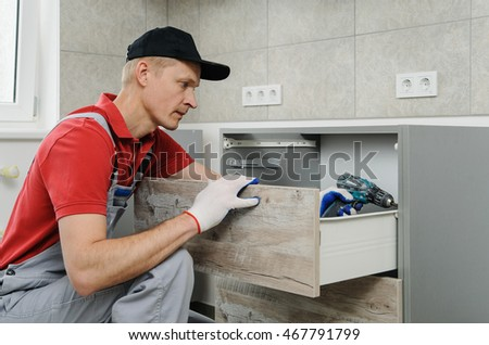 Installation of kitchen. Workman fixes the drawer in cabinet.