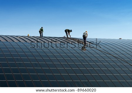 Installation of solar panels on the roof of a building - stock photo
