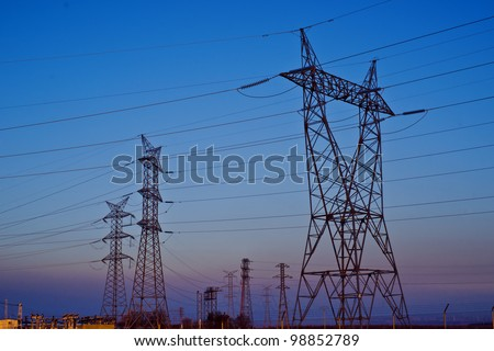 installation of towers and electric wires at sunset - stock photo