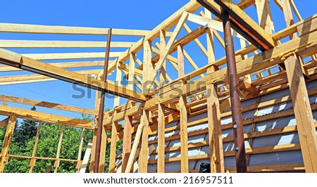 Installation of wooden beams at construction of frame house - stock photo
