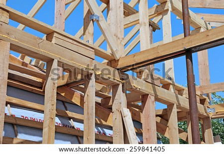 Installation of wooden beams at construction of the frame house - stock photo