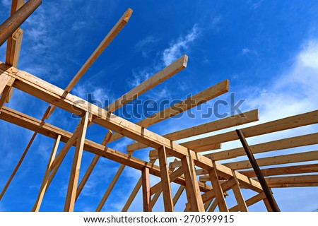 Installation of wooden beams at construction the roof truss system of the frame house - stock photo