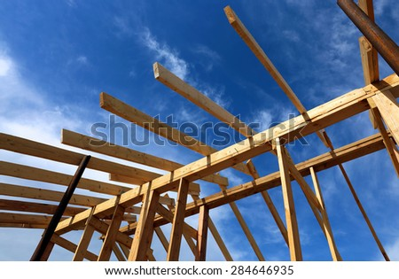 Installation of wooden beams at construction the roof truss system of the frame house